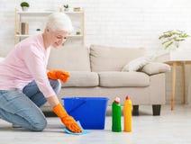 Piso maduro sonriente de la limpieza del ama de casa en casa fotos de archivo