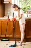 Piso moreno de la limpieza de la muchacha en cocina con la escoba y la cucharada Foto de archivo