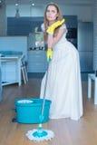 Piso que aljofifa del vestido de la mujer que lleva en cocina fotografía de archivo libre de regalías