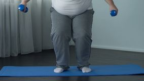 Piso que cae del hombre gordo cansado triste con pesas de gimnasia después del entrenamiento duro, desesperación almacen de metraje de vídeo