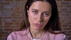 Pissed-από το πρόσωπο του καυκάσιου brunette που κοιτάζει ακριβώς και που δεν αναβοσβήνει, κόκκινο στούντιο τούβλου απόθεμα βίντεο