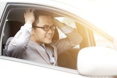 Pissed off driver. Portrait displeased angry pissed off aggressive Asian business man driving car, shouting at someone in traffic hands grabbing hair. Emotional Royalty Free Stock Photo