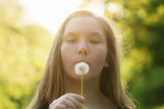 Pissenlit de soufflement de fille de l'adolescence à l'appareil-photo Images stock