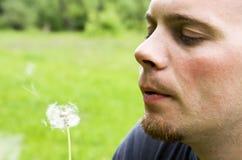Pissenlit de soufflement de jeune homme Photographie stock libre de droits