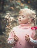 Pissenlit de soufflement de petite fille blonde photos stock