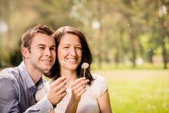Pissenlits de soufflement de couples Photographie stock libre de droits