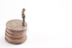 Pissing money away. Miniature man in the posture of urinating off a stack of quarters Royalty Free Stock Image