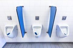 Pissoar för män på den vita väggen med blåa delningar arkivfoto