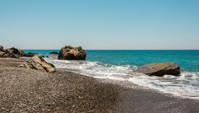 Pissouri Bay pebble beach with large rocks in a sea, Cyprus Royalty Free Stock Photo