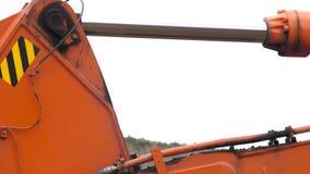 Pistão hidráulico de aço de um crescimento da máquina escavadora que levante e abaixe a cubeta durante obras Feche acima do detal filme
