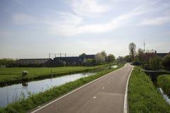 Pista ciclabile e canale in un paesaggio olandese del ploder Immagine Stock Libera da Diritti
