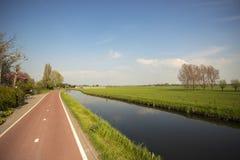 Pista ciclabile e canale in un paesaggio olandese del ploder Immagini Stock