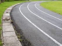 Pista corrente dell'asfalto della curva con prato inglese fotografia stock