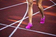 Pista corrente rossa con il corridore femminile, fine su sulle gambe Immagine Stock Libera da Diritti
