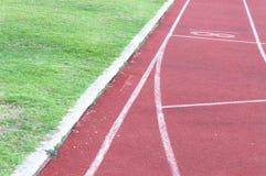 Pista corriente e hierba verde, pista corriente del atletismo directo Imagenes de archivo