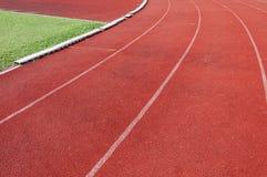 Pista corriente e hierba verde, pista corriente del atletismo directo Foto de archivo libre de regalías