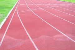Pista corriente e hierba verde, pista corriente del atletismo directo Imágenes de archivo libres de regalías
