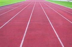 Pista corriente e hierba verde, pista corriente del atletismo directo Fotos de archivo