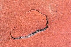 Pista corriente mojada roja agrietada en el estadio para el diseño, sitio web Fotos de archivo libres de regalías