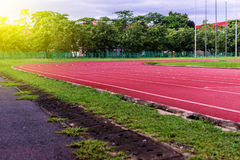 Pista corriente roja en estadio, pista corriente en el cielo azul por la mañana Imagenes de archivo