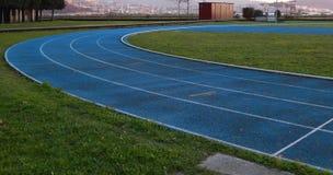 Pista de atletismo exterior no azul com linhas brancas fotografia de stock