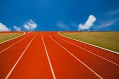 Pista de atletismo sobre o céu azul e as nuvens Fotografia de Stock Royalty Free