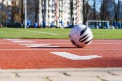 A pista de atletismo vermelha, bola no movimento, borrou jogadores de futebol no fundo Imagem de Stock