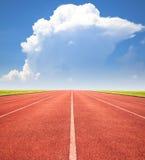 Pista de atletismo vermelha sobre o céu azul e as nuvens fotografia de stock