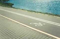 pista de bicicleta para a bordadura do exercício com a pista avante do lago/bicicleta para a bordadura do exercício com avante  fotografia de stock