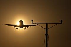 Pista de decolagem de aproximação do avião de passagem no por do sol Imagem de Stock