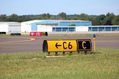 A pista de decolagem do aeroporto assina o aeródromo dos hangares fotos de stock