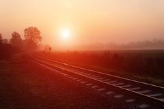 Pista de ferrocarril durante mañana de niebla del otoño Fotografía de archivo libre de regalías