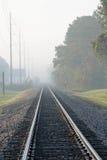 Pista de ferrocarril en niebla en mañana soleada Foto de archivo libre de regalías
