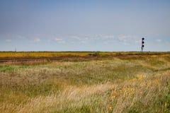 Pista de ferrocarril en pradera en verano tardío debajo del cielo azul Foto de archivo