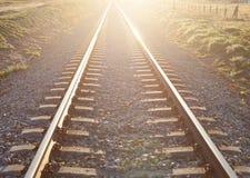 Pista de ferrocarril iluminada por el sol Foto de archivo
