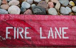 A pista de fogo stenciled em um vermelho arrastado e lascado pintou o freio com as rochas da cama de flor na parte superior fotografia de stock
