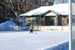 Pista de hockey sobre hielo al aire libre en última hora de la tarde con el solo patinador imagen de archivo libre de regalías