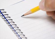 Pista de nota con el lápiz a disposición Imágenes de archivo libres de regalías