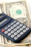 Pista de nota con la calculadora y libro y efectivo de cheque. Imagen de archivo libre de regalías