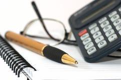 Pista de nota con la pluma, la calculadora, y los vidrios. Foto de archivo libre de regalías