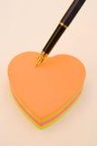 Pista de nota en forma de corazón con la pluma. Fotos de archivo