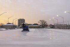 Pista de patinaje al aire libre que es limpiada para el ska de la salida del sol de la madrugada Imágenes de archivo libres de regalías