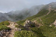 Pista de senderismo en la colina con niebla en las montañas Imagenes de archivo