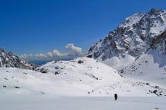 Pista de senderismo en nieve en montañas en un día soleado Imagen de archivo libre de regalías