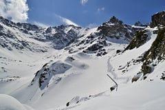 Pista de senderismo en nieve en montañas en un día soleado Imágenes de archivo libres de regalías