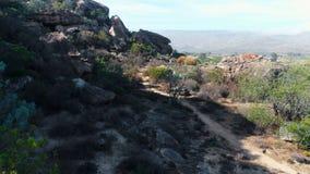 Pista de tierra que pasa con las formaciones de roca 4k metrajes