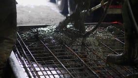 Pista del mezclador que vierte el cemento mojado a la losa reforzada del metal almacen de video