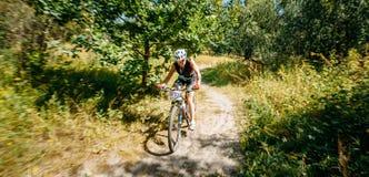 Pista del montar a caballo del ciclista de la bici de montaña de la mujer joven en bosque en el sunn Fotos de archivo