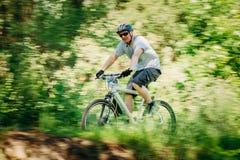 Pista del montar a caballo del ciclista de la bici de montaña en el día soleado, lifesty sano Imagenes de archivo