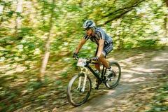 Pista del montar a caballo del ciclista de la bici de montaña en el día soleado, lifesty sano Imagen de archivo